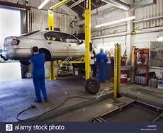 Garage Hydraulic Lift by 2 Car Mechanics Working In A Repair Garage With Hydraulic