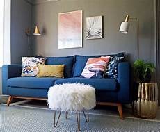 living room design blue sofa grey walls and accents in pink white and gold first blue