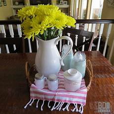 this easy everyday centerpiece starts with a basket layers in some adorable linens and is