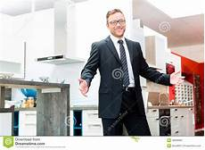 Salesman In Domestic Kitchen Furniture Showroom Stock