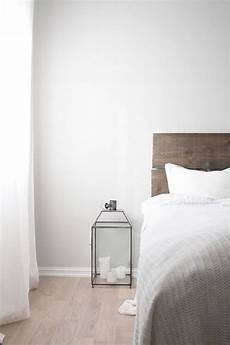 light grey walls light wooden floor white curtains grey white duvet grey wood headboard