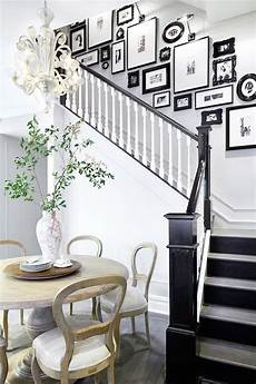 Foyer Opens To Black And White Staircase Accented With