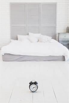 vicino al letto sveglia sul pavimento vicino al letto con lenzuola bianche