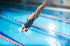female swimmer that jumping into indoor swimming pool
