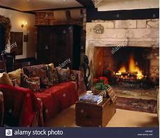 roten wurf auf sofa mit kissen neben kamin mit offenem