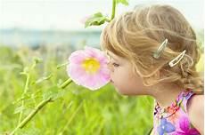 bambino sente l odore di bambina felice si siede nell erba immagine stock