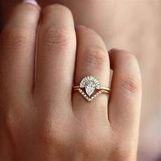pear diamond engagement ring with baguette diamond crown and chevr artemer
