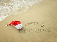 merry christmas written tropical white sand with snowman image of digit