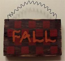distressed checkered fall sign is painted with acrylic paint in fall colors of brown
