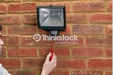 using terminal screwdriver to attach security light to brick wall thinkstock