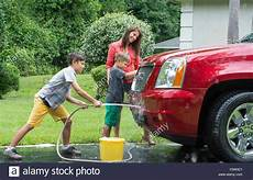 Single Washing Car At Home With Two Children In