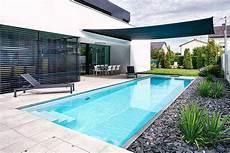 schmaler langer pool im garten mit sonnensegel pool im