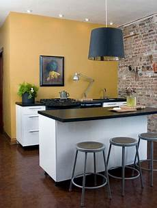 mustard yellow paint white cabinets brick accent wall hardwood flooring perfection