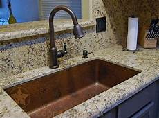copper kitchen sink faucets rubbed bronze is the color of choice to pair with hammered copper kitchen sinks as seen in