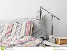 vicino al letto lada e libri su una tavola laterale vicino al letto