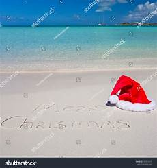 santa hat white and merry christmas written in the sand 193914815