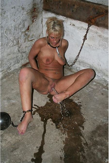 Cute blonde slave girl is chained up tightly inside her ...