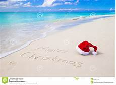 merry christmas written white sand with image of coastline christmas