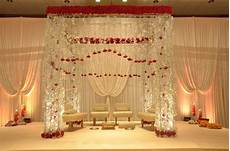 crystal mandap design with hanging red roses the perfect