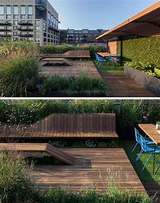 this rooftop deck has custom designed benches surrounded by greenery