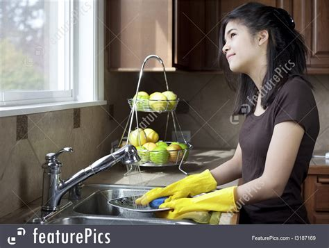 daily life teen girl washing dishes stock picture