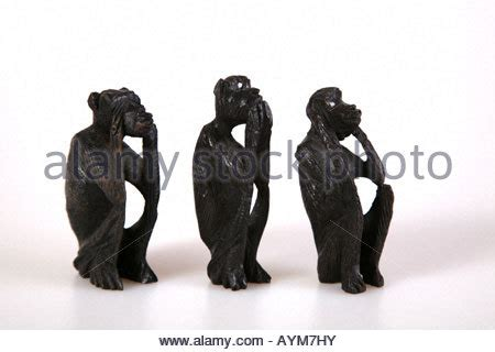 three wise monkeys figurines of wood on a black background stock royalty free