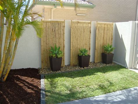 garden feature wall colours tall planters and rocks against wall lined by stones small yard landscape ideas pinterest