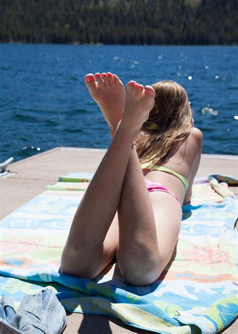 teen bikini teen girl laying on a dock in her bikini stocksy united