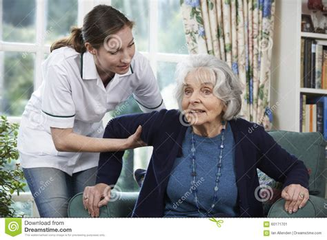 care worker helping senior to get up out of chair