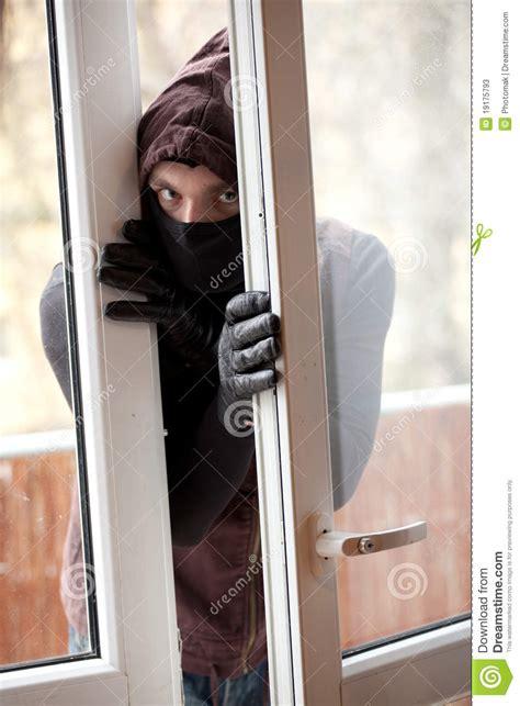 Burglar Breaking Into A House Through Window Royaltyfree