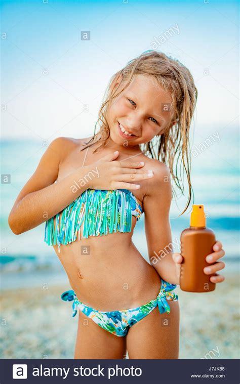 cute  girl aplicar bronceador en la playa  mirando