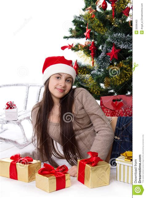 teen girl in santa hat with gifts under christmas tree