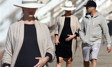 Pregnant Rosie Huntington-Whiteley lovingly pats her bump ...