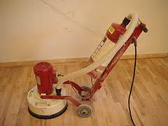sanding a new hardwood floor with a rental drum sander