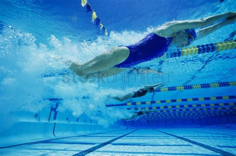 Female Swimmers Racing Underwater In Pool Stock Photo