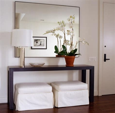 small white entry table slipcovered white ottomans and modern wood console table