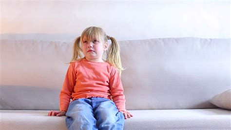 Little girl sitting on couch and crying, mother screaming ...
