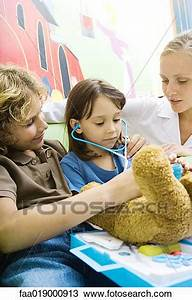 Stock Photo of Boy and girl playing doctor with teddy bear ...