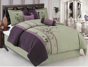 purple and green bedding set with floral pattern plus pillows placed on the black leather bed