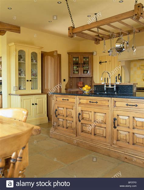 yellow country kitchen hanging wooden utensil rack above island unit in 1209
