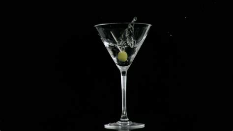 martini glass background olive falling in super slow motion in a cocktail against