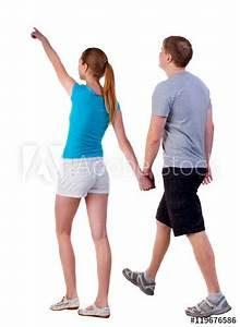 """""""Back view of walking young couple (man and woman ..."""