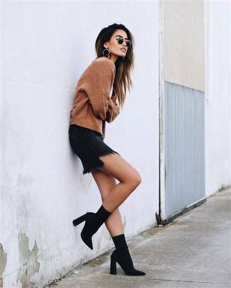 Picture Of an ocher sweater a denim mini skirt and black suede sock boots