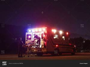 EMTs loading patient onto ambulance at night stock photo ...