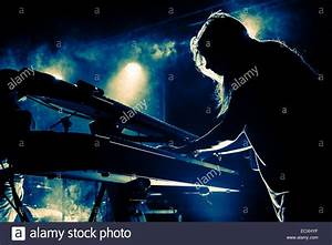 Silhouette of a girl playing keyboard on stage during a ...