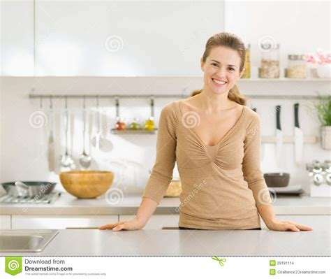 Moderne Hausfrau by Portrait Of Smiling In Modern Kitchen Stock