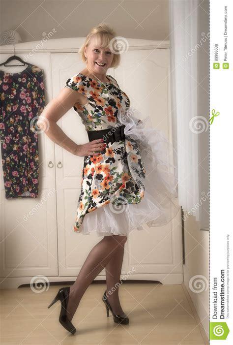 elderly woman wearing  floral print dress stock photo