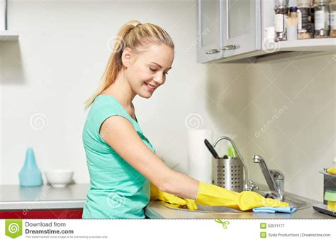 cleaning houses under the table happy woman cleaning table at home kitchen stock photo