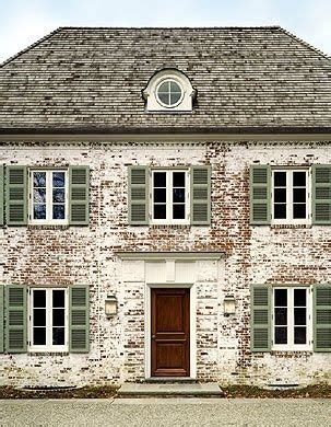 faded white painted brick wooden door green shutters old country home sweet home in