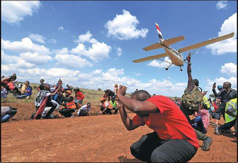 Spectators React As A Plane Flies Over Them During The